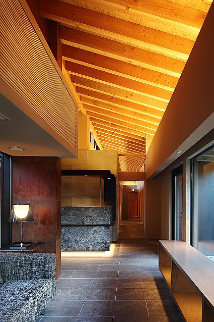 木構造部材を意匠化した待合室と受付の内観。高級旅館のような内装。