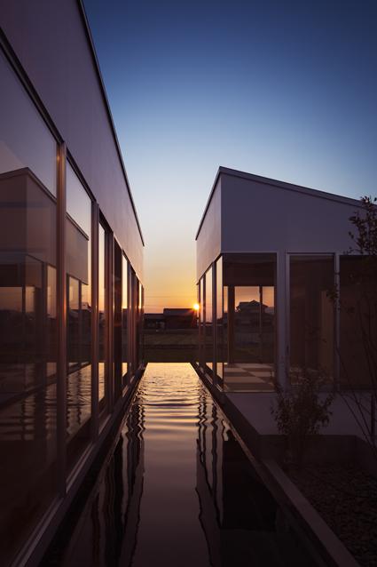 水盤の夕日とリビングと離れの徳島鳴門の平屋の住宅外観設計
