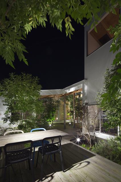 コートハウス中庭のアウトドアリビングダイニングの夜景住宅設計