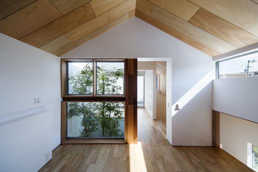 家型蔵の中庭吹抜け植栽を見る木壁の愛媛の寝室住宅設計