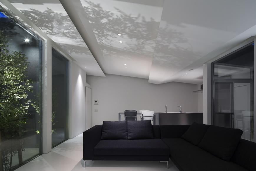 平屋のワンルームリビングダイニングの中庭白い床の三重の住宅設計
